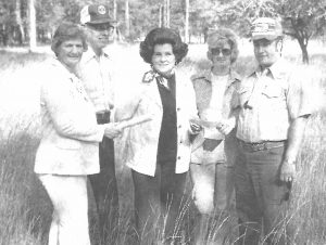Photograph of 4 people in a citrus grove including Dr. Thomas B. Mack
