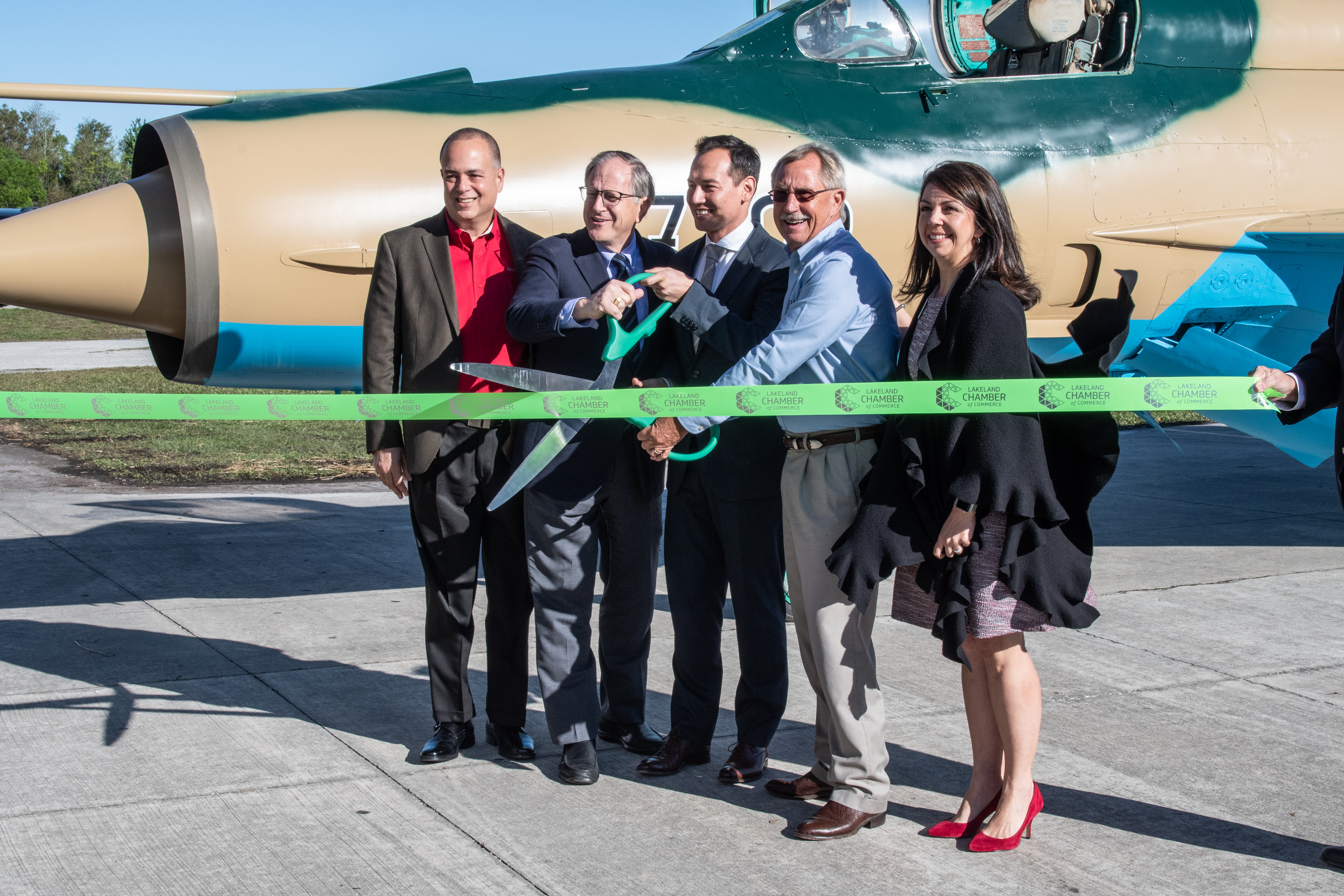 Florida Air Museum and Draken officials standing in front of MiG-21 ribbon cutting.